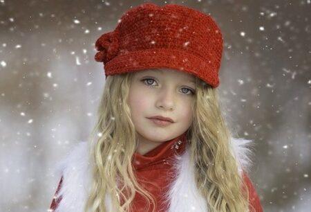 雪の中にたたずむ赤い帽子をかぶった女の子